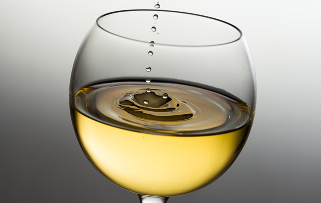 Pouring white wine drop by drop