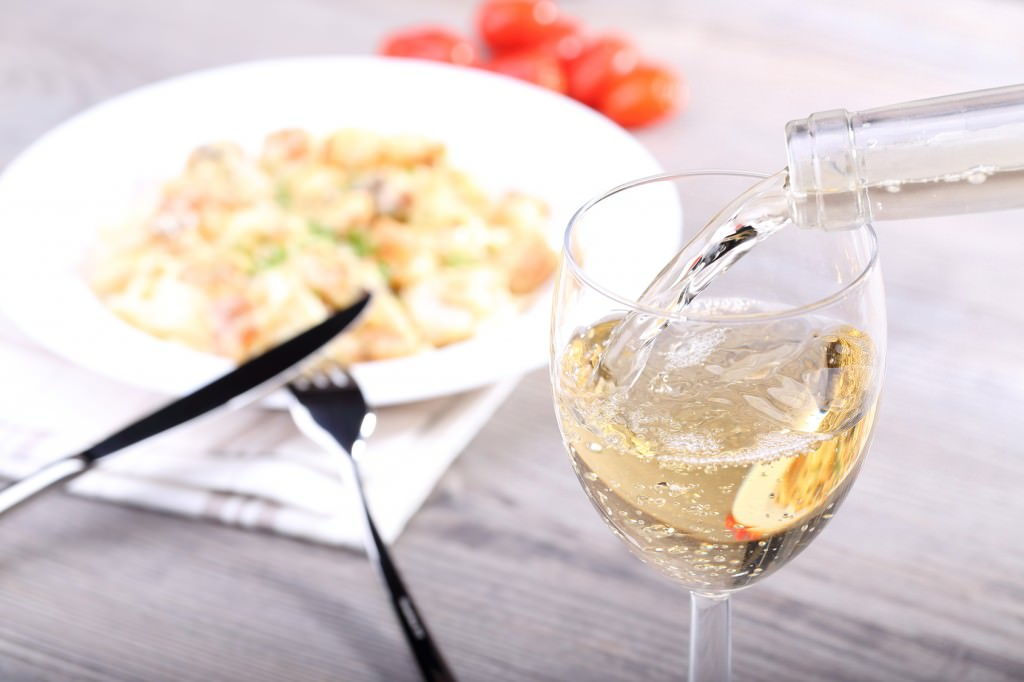 Pouring wine and pasta with salmon